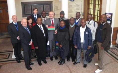 """Nine government officials participated in an """"interactive knowledge transfer"""" at the University of Dundee's Centre for Energy, Petroleum and Mineral Law and Policy this week. Director of the Centre, Professor Peter Cameron is feature centre, holding the Malawian flag (Photo courtesy of CEPMLP News)"""